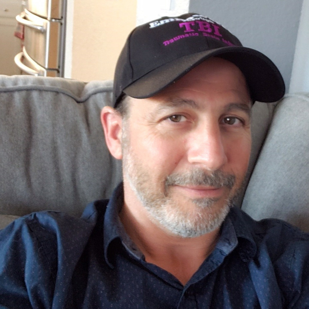 image of a man with a gray beard wearing an Empowered Through TBI hat