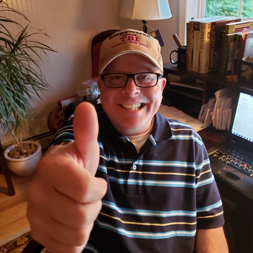 image of a man wearing glasses and an Empowered Through TBI hat with his thumb up