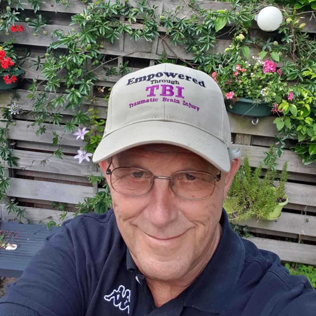 image of a man in glasses wearing an Empowered Through TBI hat, with flowers growing behind him