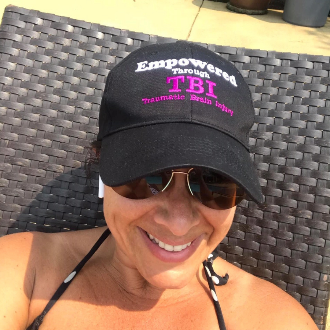 image of a woman wearing sunglasses and an Empowered Through TBI hat
