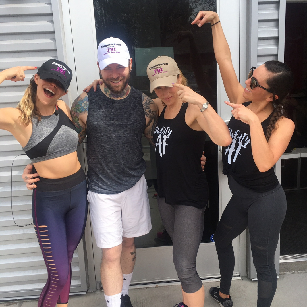 image of 3 women and a man wearing Empowered Through TBI hats