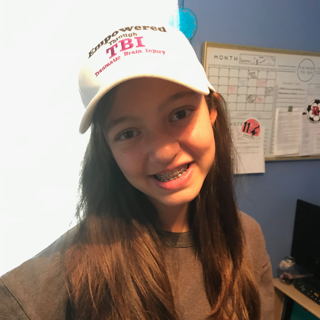 young girl with braces wearing an empowered through TBI hat